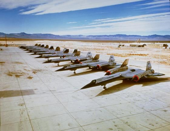 OXCART aircraft on the ramp at Groom Lake Area 51 in 1964. There are ten aircraft in the photo; the first eight are OXCART machines, and the last two are Air Force YF-12As